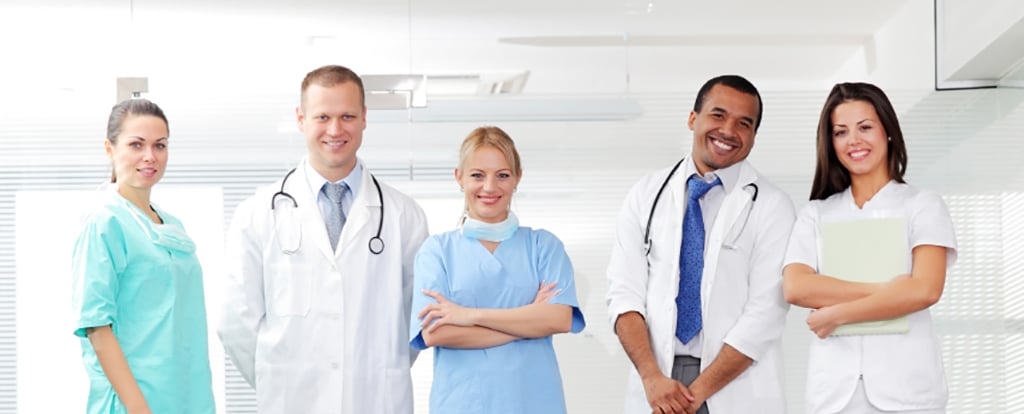 Smiling medical people with stethoscopes, standing and looking at camera. Doctors and nurses.
