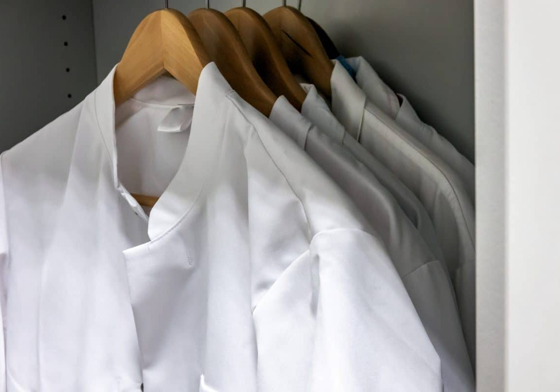 White smocks on wooden hangers hang in the cupboard of a laboratory.