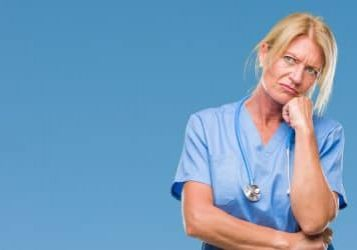 Middle age blonde nurse surgeon doctor woman over isolated background thinking looking tired and bored with depression problems with crossed arms.