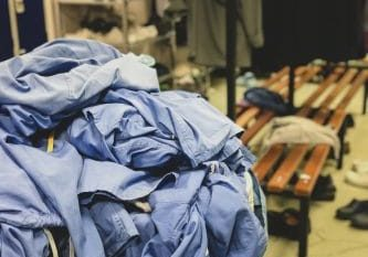 A clothes basket overflowing with surgical scrubs in the changing room of a hospital in the United Kingdom. This is seen often at the end of the day or on Sunday night.