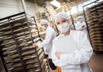 Woman working at a food factory with a group of people - quality control concepts