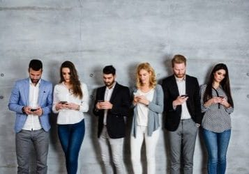 Group of business people standing against the wall and typing message on their smart phone