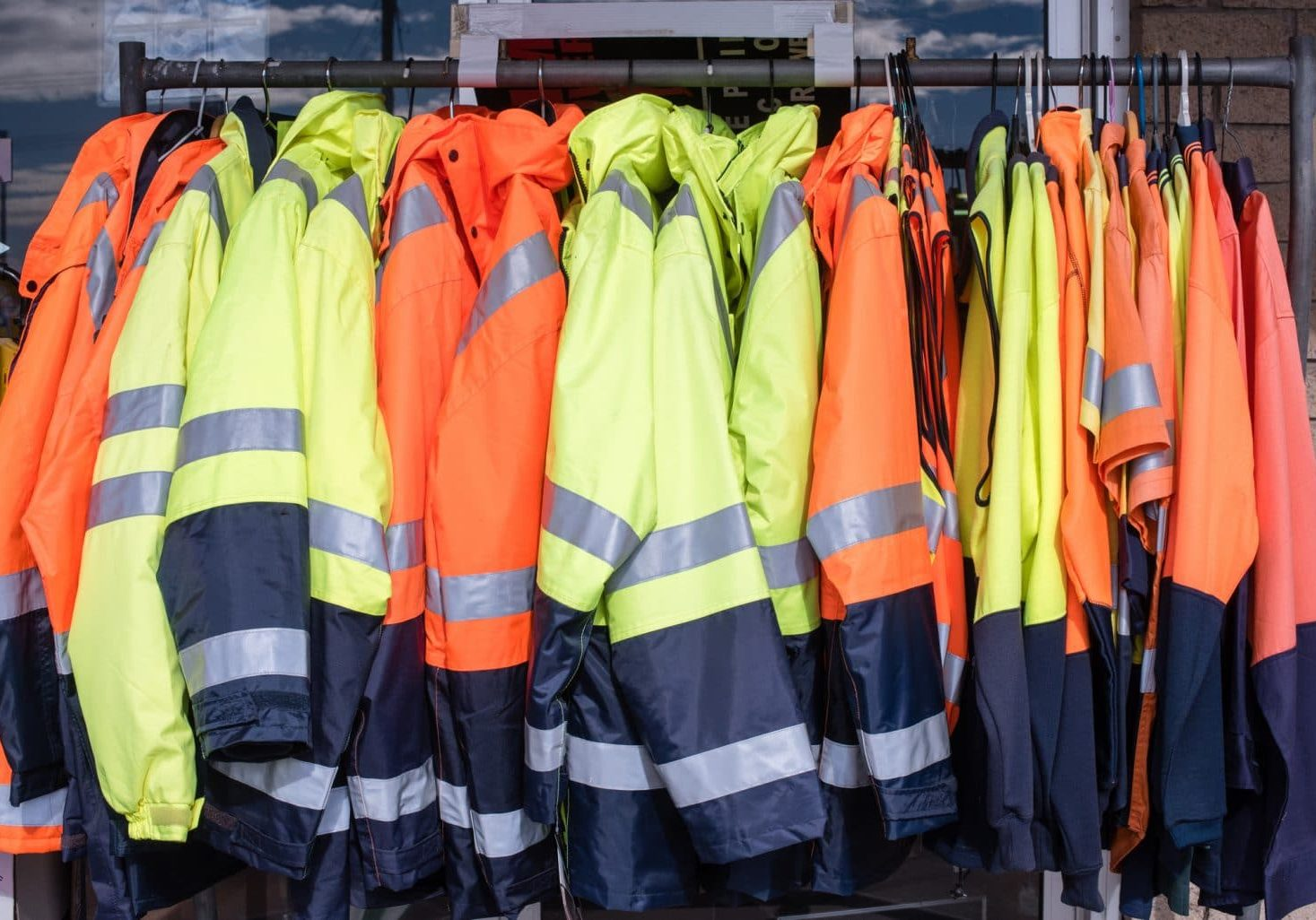 Full frame view of yellow and orange high visibiity protective clothing on rack