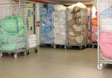 Bags With Dirty Laundry Sheets in Rolling Carts